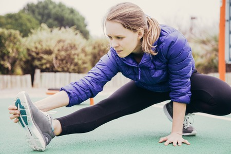 Focused athlete girl warming up outside. Young woman in sports winter jacket stretching leg on playground. Autumn or winter training concept