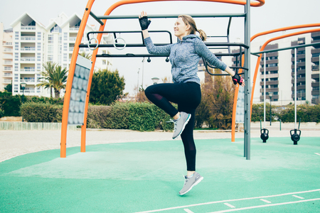Cheerful jogger exercising outside. Young woman doing cardio training on outdoor sports ground. Cardio training concept Reklamní fotografie