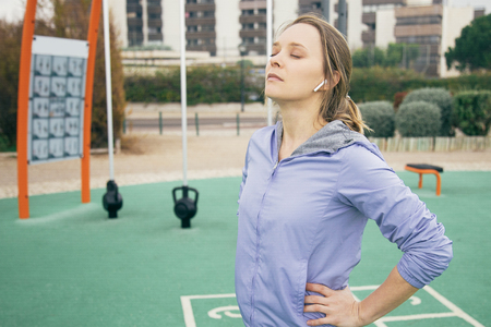 Peaceful fit girl closing eyes and concentrating before morning exercising. Young woman in sports hoody standing on outdoor playground and inhaling fresh air. Outdoor exercising concept