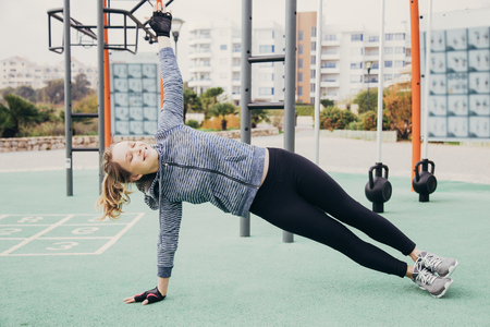 Positive sporty girl excited with outdoor workout. Young woman in hoody and tights holding side plank and smiling with closed eyes. Core training concept