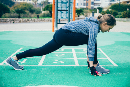 Focused serious jogger training on outdoor playground. Fit young woman stretching legs and hips. Stretching body concept