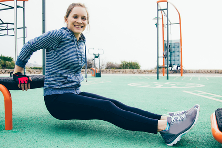 Joyful sporty girl working on arm muscles. Young woman in hoody and tights doing triceps bench dips on playground and smiling at camera. Body training concept Reklamní fotografie
