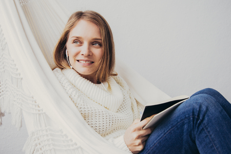 Pensive young woman in earphones thinking about new project and making notes in organizer. Smiling lady in sweater and jeans sitting hammock. Creative ideas concept Banco de Imagens