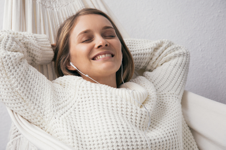 Smiling dreamy young woman relaxing in hammock. Excited lady in white sweater holding hands behind head and listening to music in earphones. Resting concept
