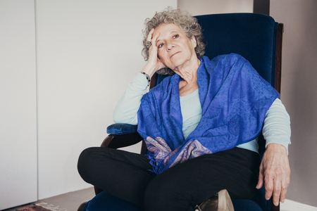 Pensive senior lady sitting in rocking chair and looking away. Calm old woman with curly hair relaxing at home. Contemplation concept