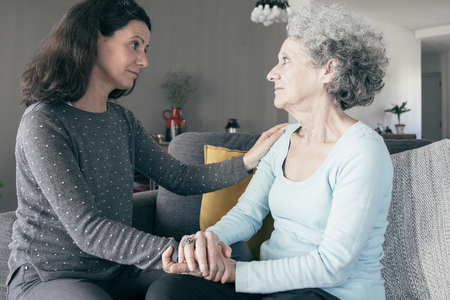 Woman holding elderly mother hands and supporting her. Mother and daughter talking and sitting on couch with home interior in background. Caring for aging parents concept.