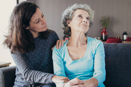 Woman holding hand on senior mother shoulder and comforting her. Mother and daughter talking and sitting on couch with home interior in background. Caring for aging parents concept.