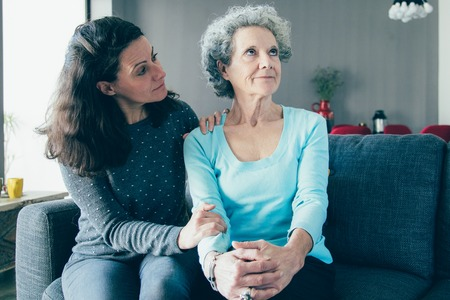 Woman holding hand on senior mother shoulder and supporting her. Mother and daughter talking and sitting on couch with home interior in background. Caring for aging parents concept.