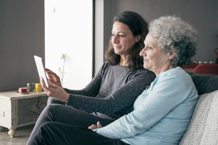 Focused senior woman and her daughter using tablet computer. Mother and daughter sitting on couch with home interior in background. Technology concept.