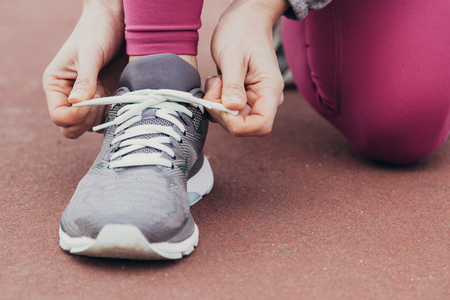 Close-up of runner tying lace of sport shoe while preparing for race. Unrecognizable woman tying bow on jogging shoe. Sport shoe concept Standard-Bild