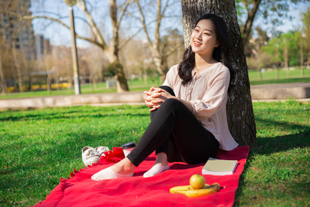 Delighted Asian girl enjoying break in city park. Young woman sitting on red blanket near fruit, coffee cup and book. Leisure time outdoors concept