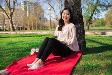 Joyful positive Asian girl enjoying weekend outdoors. Young woman sitting on red blanket, leaning back on tree, holding paper cup and smiling at camera. Leisure in city park concept Stock Photo