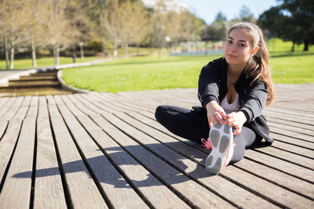 Content young lady stretching leg in city park. Pretty woman wearing sportswear and sitting on wooden floor with green lawn in background. Outdoor workout concept. Front view. 스톡 콘텐츠