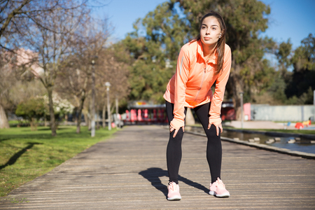 Sporty young lady leaning on knees and relaxing in city park. Woman wearing sportswear and standing on wooden floor with trees in background. Workout concept. Front view.