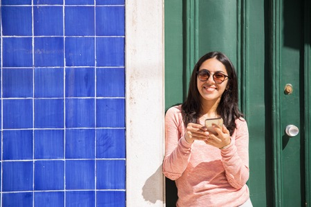 Happy woman using smartphone outdoors. Pretty young lady looking at camera and standing at door and wall. Communication concept. Front view.