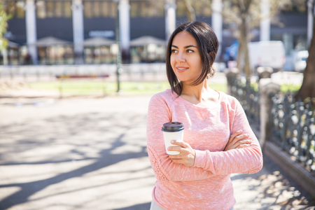 Smiling young woman holding plastic coffee cup outdoors. Pretty lady drinking coffee and standing with spring city view in background. Urban lifestyle concept. Imagens - 121627253
