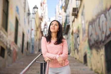 Zrelaksowany młoda kobieta opierając się na poręczy schodów miasta. Ładna pani stojąca z graffiti ścianami w tle. Koncepcja miejskiego stylu życia. Przedni widok.