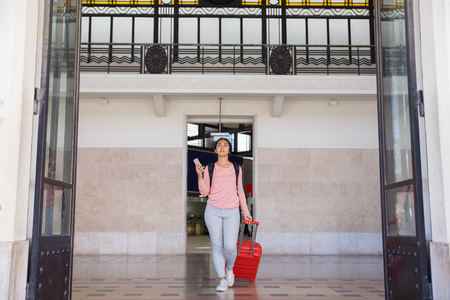 Serious woman pulling trolley case in station hall. Pretty young lady holding smartphone and walking. Tourism and travel concept. Front view.