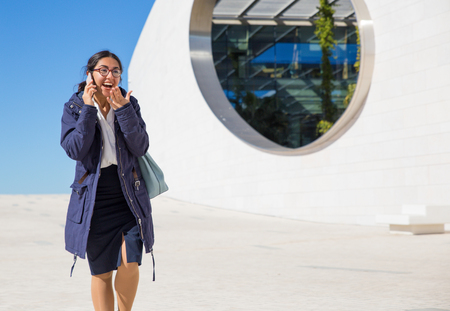 Positive surprised manager talking on phone on her way to office. Young woman in formal clothing and overcoat walking outdoors, talking on cell, gesturing and laughing. Communication concept Stock Photo