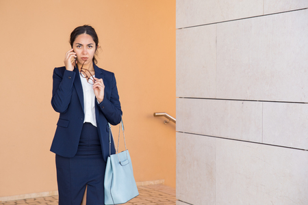 Serious business lady speaking on mobile phone and listening to talk partner carefully. Pensive young woman touching lips with eyeglasses temple and talking on cell. Important phone call concept