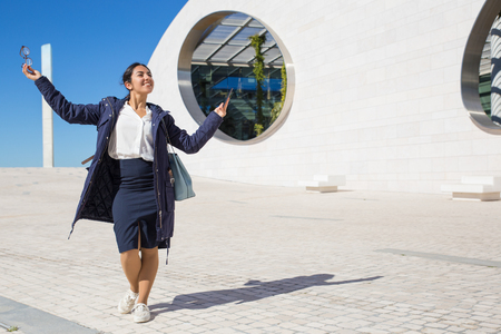Happy excited manager having fun outdoors. Joyful business woman in formal clothing and overcoat holding smartphone and eyeglasses and posing with spread hands. Business success concept Reklamní fotografie - 120939218