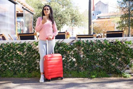 Młoda kobieta z bagażem stoi na dworcu autobusowym. Atrakcyjna dziewczyna Indian w odzieży casual przy użyciu smartfona podczas sprawdzania rozkładu jazdy autobusów. Koncepcja podróży Zdjęcie Seryjne