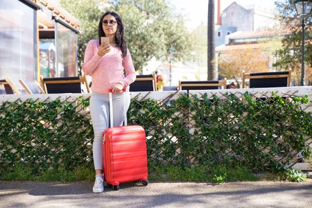 Young woman with luggage standing at bus station. Attractive Indian girl in casual clothing using smartphone while checking bus timetable. Trip concept