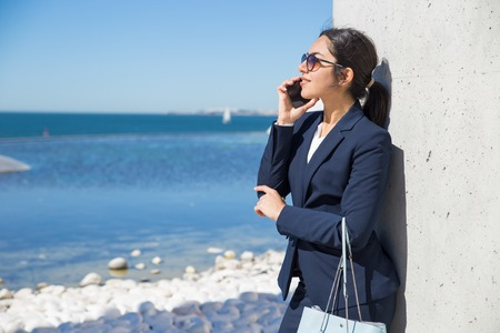 Smiling pensive businesswoman standing by sea and enjoying nice phone talk. Young woman in office suit and sunglasses speaking on cell and admiring seascape. Work break by sea concept