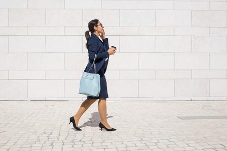 Ernster Profi zu spät zur Arbeit und trinkt Kaffee zum Mitnehmen auf der Flucht. Junge Geschäftsfrau im Anzug, die im Freien spazieren geht, Handtasche und Kaffee zum Mitnehmen trägt. Morgen Weg zum Bürokonzept Standard-Bild