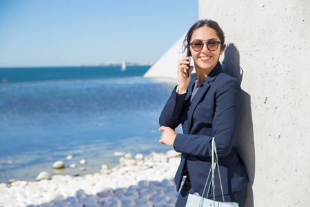 Joyful business lady learning good news from phone call. Happy young woman in office suit and sunglasses talking on cellphone and smiling at camera. Business phone talk concept