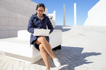 Portrait of confident young woman working on laptop outdoors. Asian businesswoman wearing glasses sitting on bench in modern urban environment. Freelancer concept 写真素材