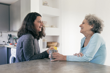 Positive woman visiting retired mother. Senior elegant woman meeting with daughter over cup of tea and laughing. Care of parents concept Фото со стока