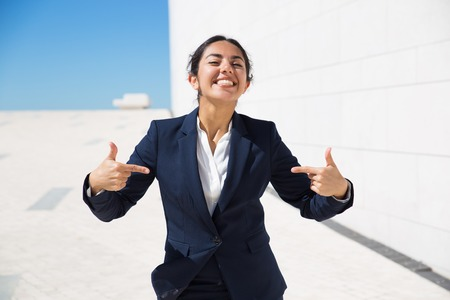 Happy excited candidate convincing to hire her. Happy positive young business woman in formal suit standing outside, posing and pointing fingers at herself. Confident professional concept