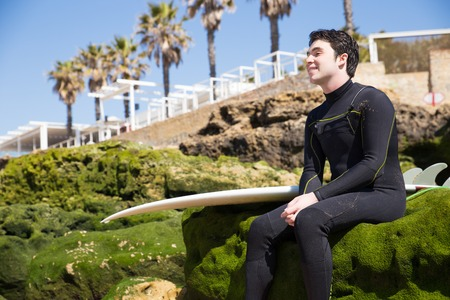 Relaxed man sitting on mossy rocks with surfboard. Handsome young guy wearing wetsuit with palm trees and beach constructions in background. Surfboarding and vacation concept. 写真素材 - 121629179