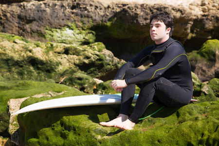 Serious man sitting on mossy rocks with surfboard. Handsome young guy wearing wetsuit. Surfboarding and vacation concept. 写真素材