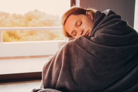 Sick young fair-haired Caucasian woman covered with grey blanket sitting on grey sofa in living room with closed eyes, embracing her knees, turning head to camera. Illness, lifestyle concept Stock Photo