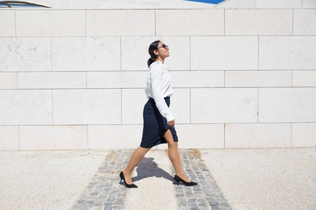Smiling businesswoman on her way to office. Side view of young woman in formal shirt and sunglasses walking along outdoor wall. Way to work concept