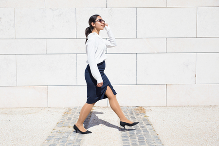 Positive business professional hurrying to office. Woman in formal shirt and sunglasses walking along outdoor wall. Walking to work concept