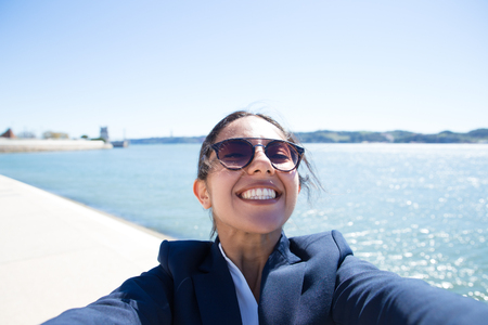 Positive excited office worker having fun outside. Selfie of cheerful young woman in formal jacket walking on promenade by river. Self portrait concept 写真素材
