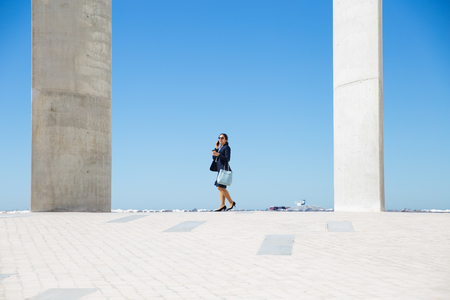 Estate agent talking to customer on phone. Wide shot of young business woman walking along promenade and turning face to camera. Work by sea concept Reklamní fotografie - 121629119