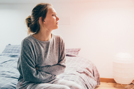 Tired sick woman in grey homewear sitting on bed, keeping hands on stomach, suffering from pain, looking aside. Illness, stomach ache concept Stock fotó