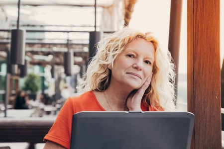 Pensive freelance blogger working on article in outdoor cafe. Dreamy middle aged woman in casual using laptop. Freelance concept Stock Photo - 121628894