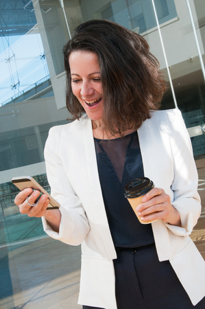 Portrait of excited businesswoman with coffee texting message. Mid adult woman using smartphone outdoors at coffee break. Coffee break and communication concept