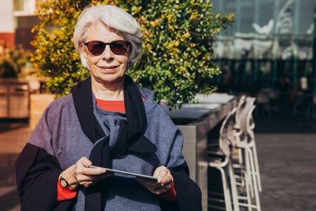 Cheerful senior tourist walking and using navigator app. Grey haired mature woman in sunglasses and overcoat standing outdoors and holding tablet. Digital gadget concept 免版税图像