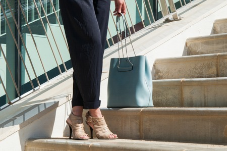 Medium shot of female crisscrossed legs in black trousers with blue bag standing at stairs. Side view. Lifestyle concept Stock Photo
