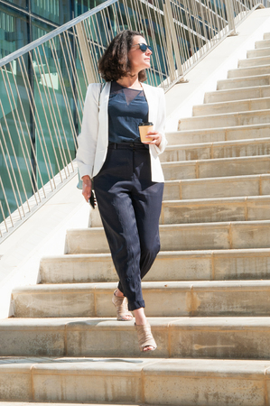 Serious good looking businesswoman in white jacket with blue bag walking downstairs, turning head aside, enjoying sun, holding coffee and phone in hands. Lifestyle concept