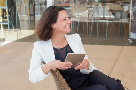 Happy relaxed elegant lady using tablet in outdoor cafe. Woman in white casual jacket sitting in rattan chair, holding gadget, looking away and laughing. Leisure concept