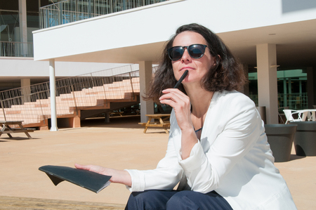 Inspired writer creating new story. Pensive woman in sunglasses sitting near modern building, touching chin with pen and holding notebook. Writing and creativity concept