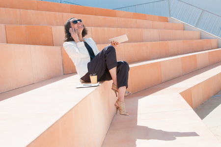Joyful professional learning funny news from phone talk. Woman in office jacket sitting outdoors with cup of coffee and tablet, speaking on cellphone and laughing out loud. Work break and fun concept Banque d'images - 120944446