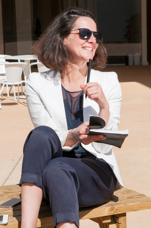 Happy cheerful blogger drafting plan of article. Pensive woman in sunglasses and office jacket sitting on outdoor terrace, taking notes and smiling. Writing outside concept